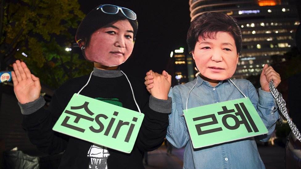 "Protestors wearing masks of South Korean President Park Geun-Hye (R) and her confidante Choi Soon-Sil (L) pose for a performance during a rally denouncing a scandal over President Park""s aide in Seoul on October 27, 2016"