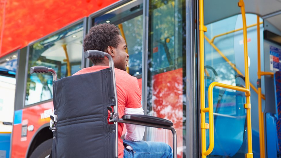 Man in wheelchair waiting by bus