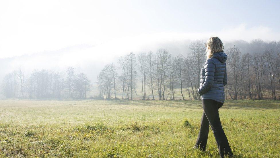 Mujer caminando en bosque