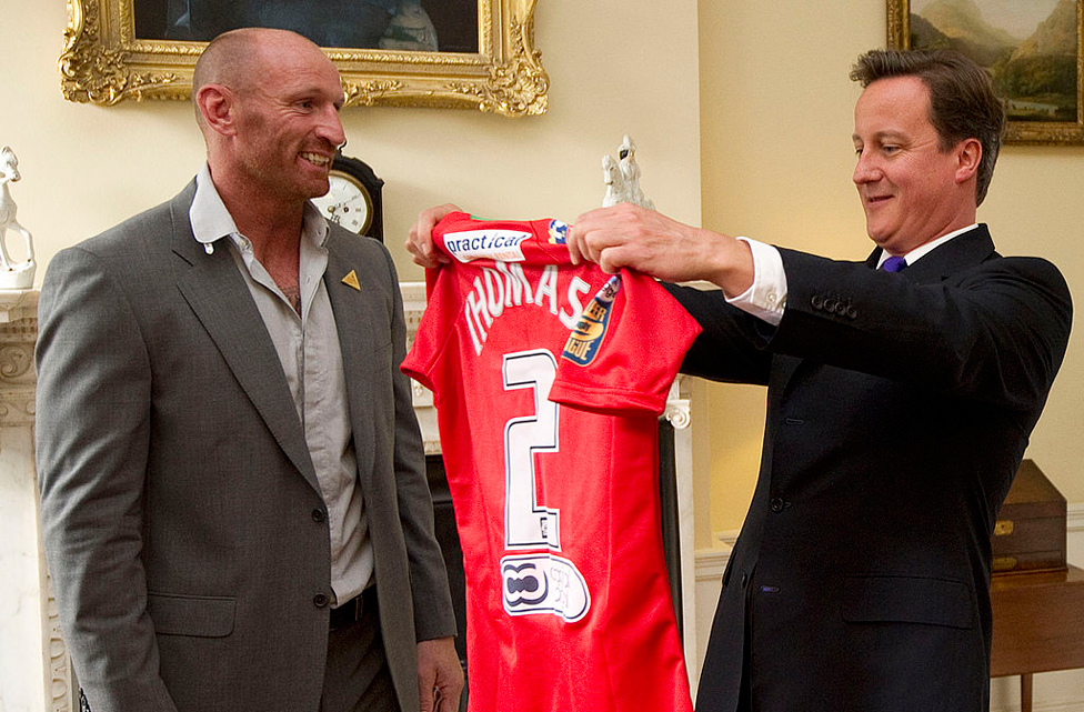 Presenting a shirt to then Prime Minister David Cameron in 2011 at a meeting of sports figures to discuss homophobia and transphobia in sport