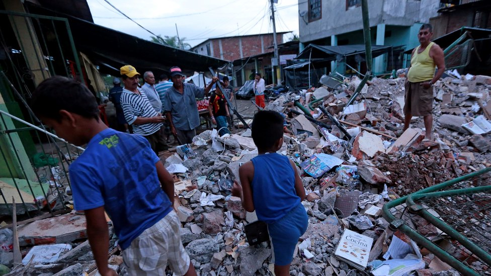 People look through rubble after a quake in Ecuador
