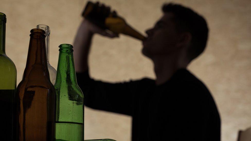 Sombra de hombre joven bebiendo alcohol.