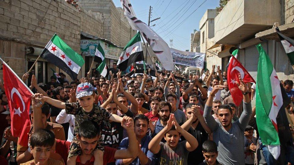 İdlib'in 20 kilometre kuzey batısında, muhaliflerin elindeki Hazanu kasbasında Cuma günü yapılan bir gösteri