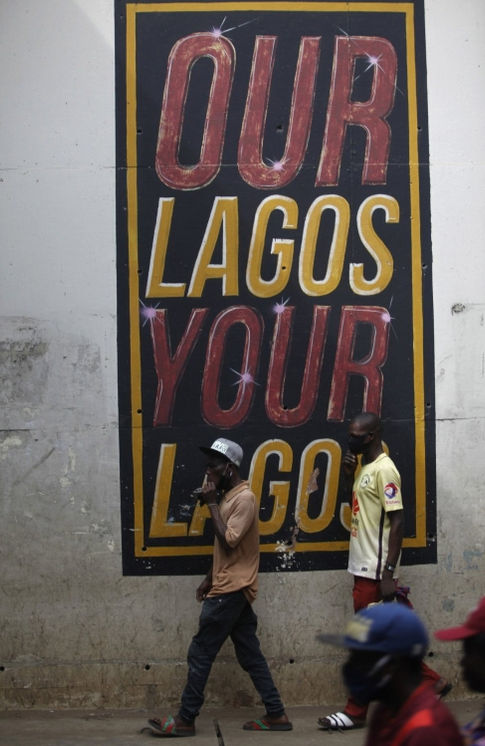"""Men wearing face masks walk past a mural reading """"Our Lagos, Your Lagos""""."""