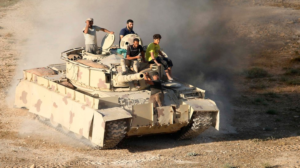 Syrian rebel fighters ride a tank in Deraa, south-western Syria, on 23 June 2018