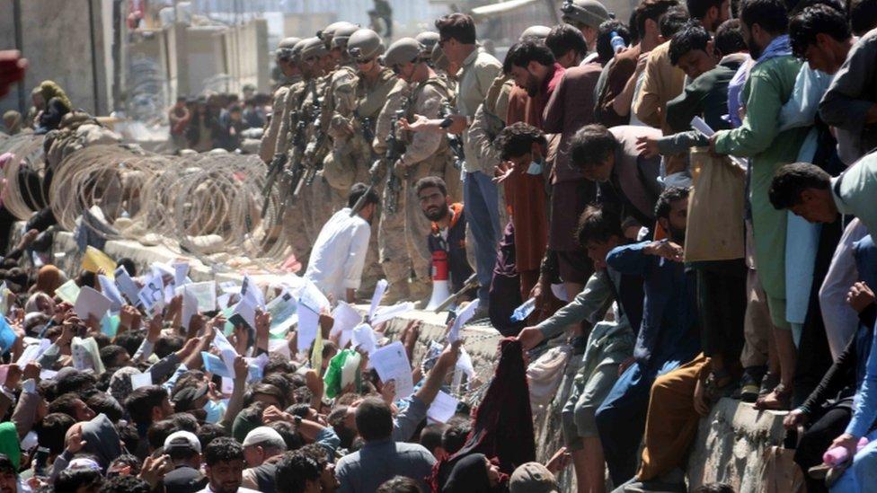 Afganos muestran credenciales en el aeropuerto para tratar de salir del país.
