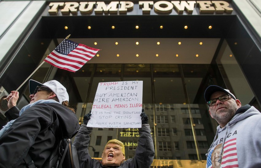 A protester holds up a sign outside Trump Tower