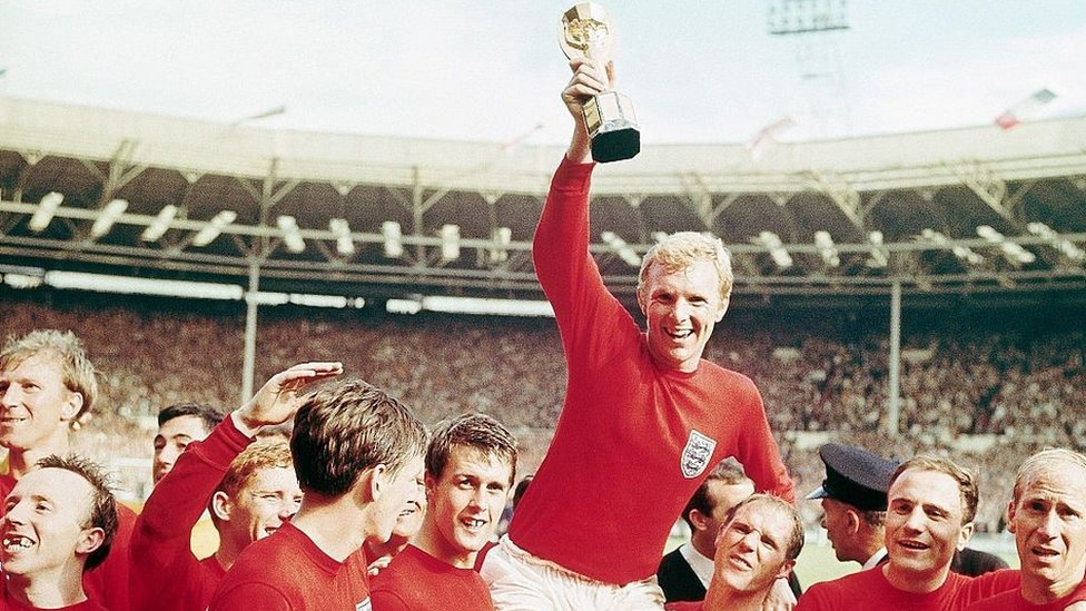 Bobby Moore holds the Jules Rimet trophy while carried on the shoulders of his team mates