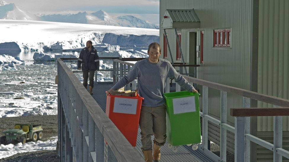 Man carrying waste recycle bins at Rothera research station