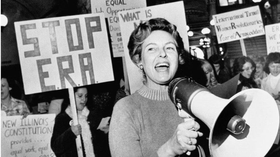 Phyllis Schlafly with protesters behind her holding signs saying 'Stop ERA'