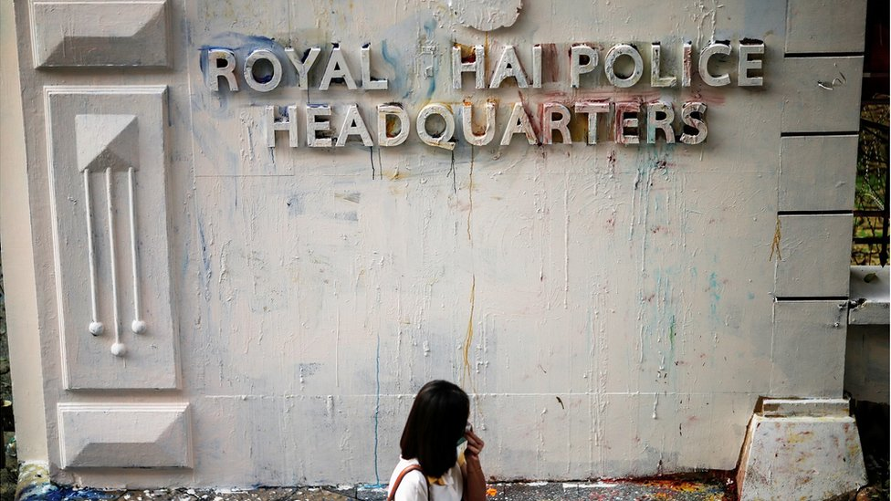 A woman reacts while walking past the damaged signage of the police headquarters