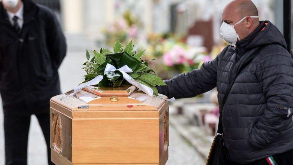 Hombre acompaña el féretro de una víctima de coronavirus.