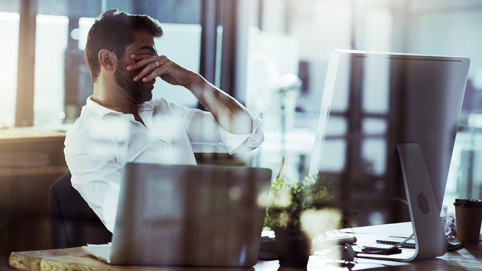 Trabajador cansado frente a una computadora.