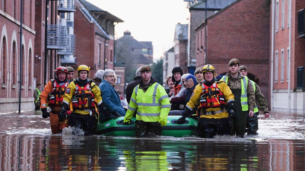 Members of the Army and rescue teams help people in York