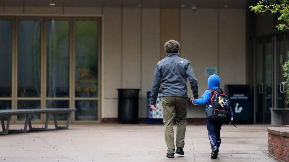 Un padre de espaldas acompaña a un niño a la escuela.