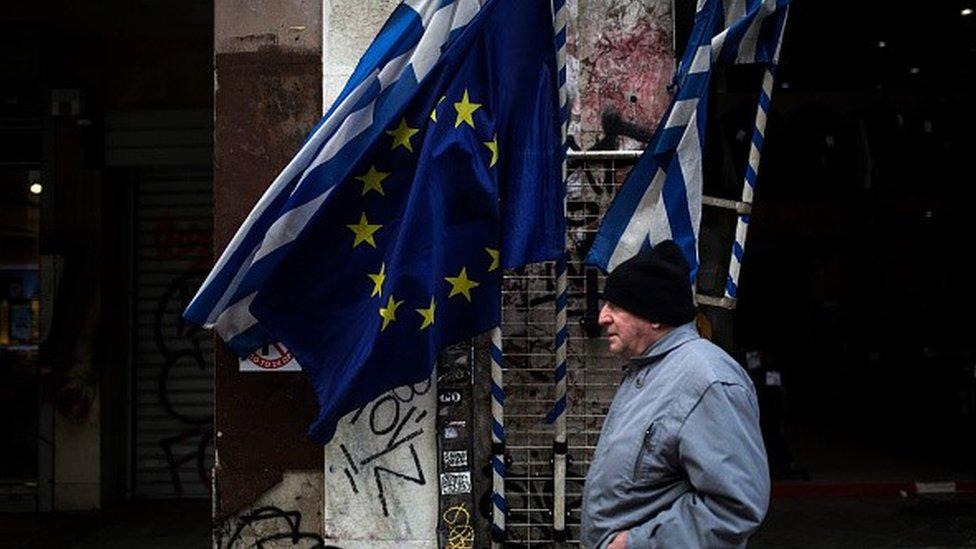 Man walking past Greek and EU flags