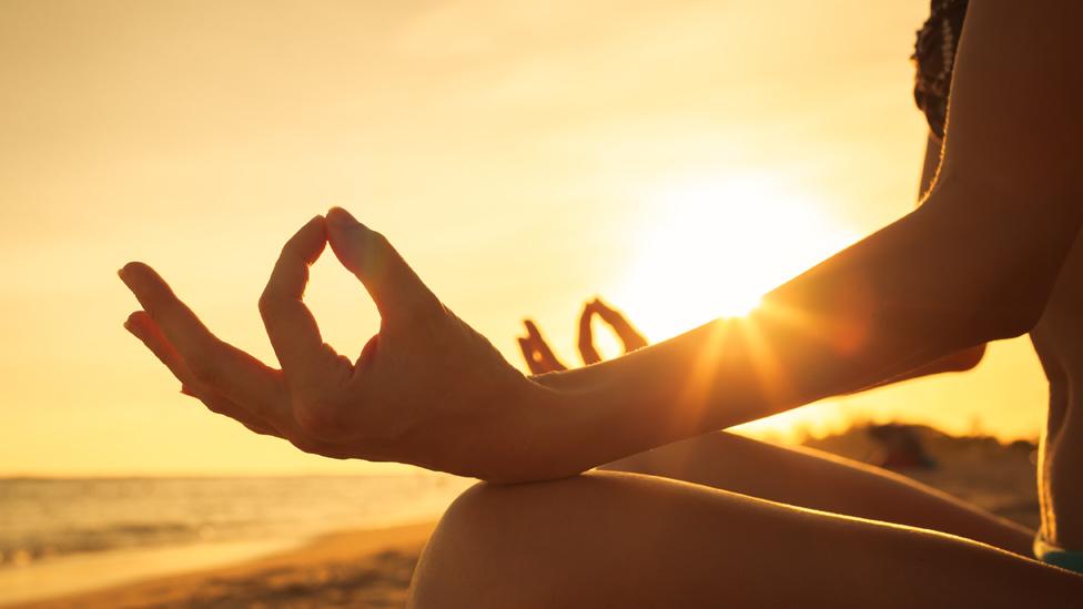 Manos de una mujer en posición de yoga durante una puesta de Sol