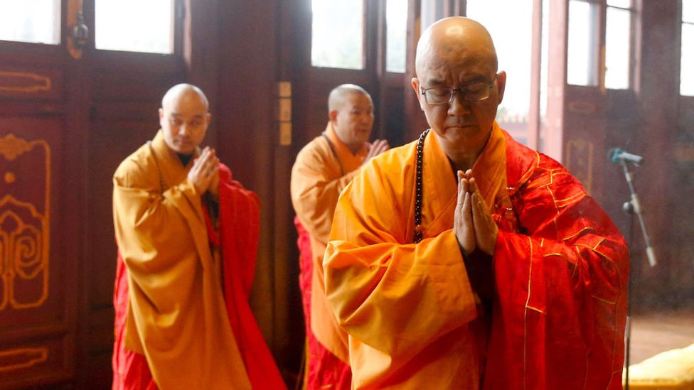 This photo taken on February 12, 2016 shows Xuecheng (R), the abbot of Beijing's Longquan Monastery, praying during a ceremony
