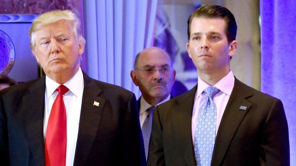 ترامب وبجواره نجله وخلفهما وايسلبرغ، المدير المالي لمنظمة ترامب