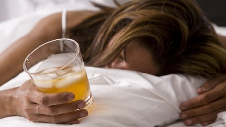 Woman in bed holding drink