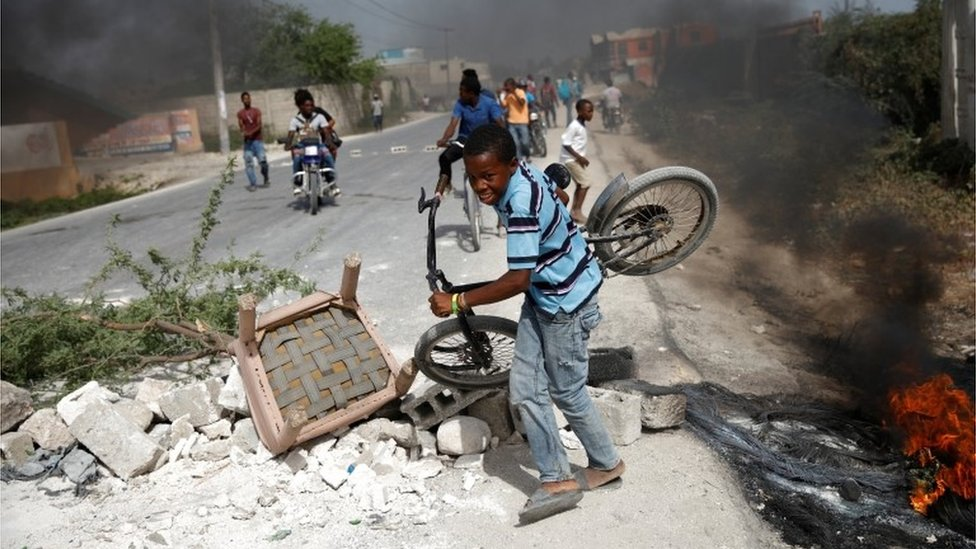 A boy carrying his bicycle passes through a barricade on the outskirts of Croix-des-Bouquets, Haiti, July 8, 2018.