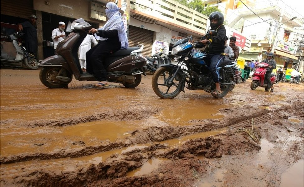 Indian cars, scooters, and motorists drive on a damaged road consists of water logged and potholes following recent heavy rains, in Bangalore, India, 12 October 2017