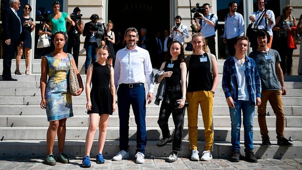 Greta Thunberg and other youth climate activists stand outside France's parliament