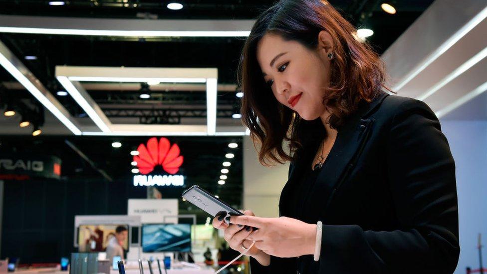 امرأة تنظر إلى هاتف محمول من إنتاج شركة هواوي
