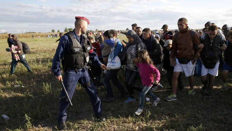 Migrants leave a collection point in Roszke, Hungary, 7 Sep