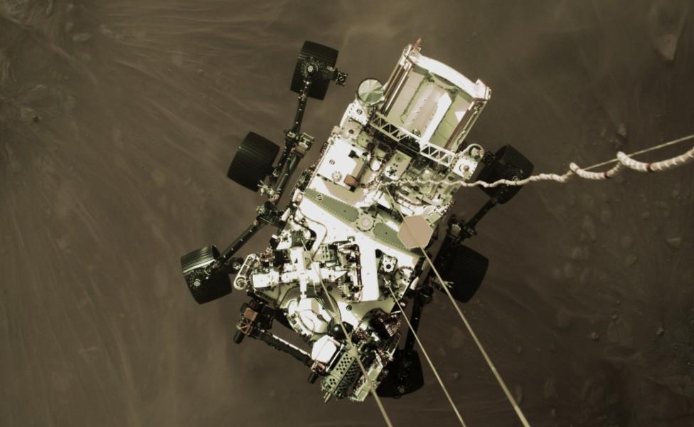 Perseverance descendiendo al suelo de Marte sujetado por cables de nylon