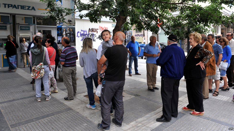 People stand in a queue to use ATM machines at a bank in Thessaloniki on 27 June 2015.