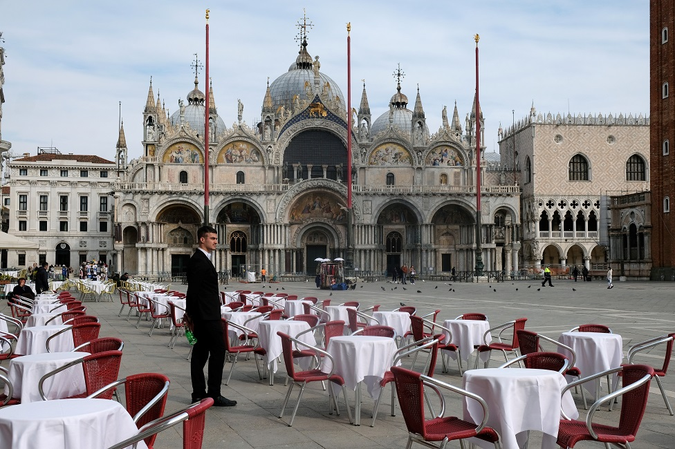 A waiter stands by empty tables outside a restaurant at St Mark