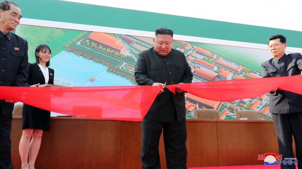 Kim Jong-un cortando la cinta de una fábrica.