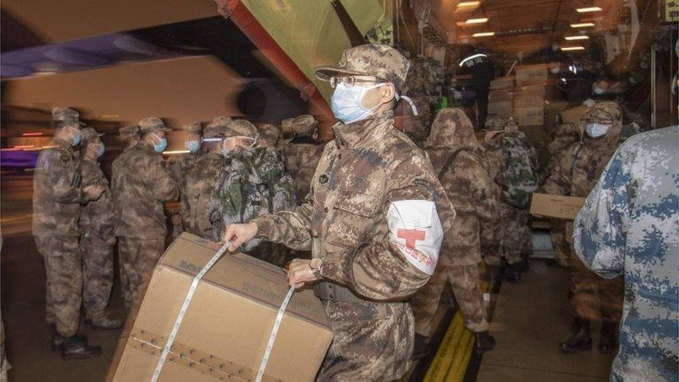 Médicos militares bajan suministros de un gran avión en Wuhan