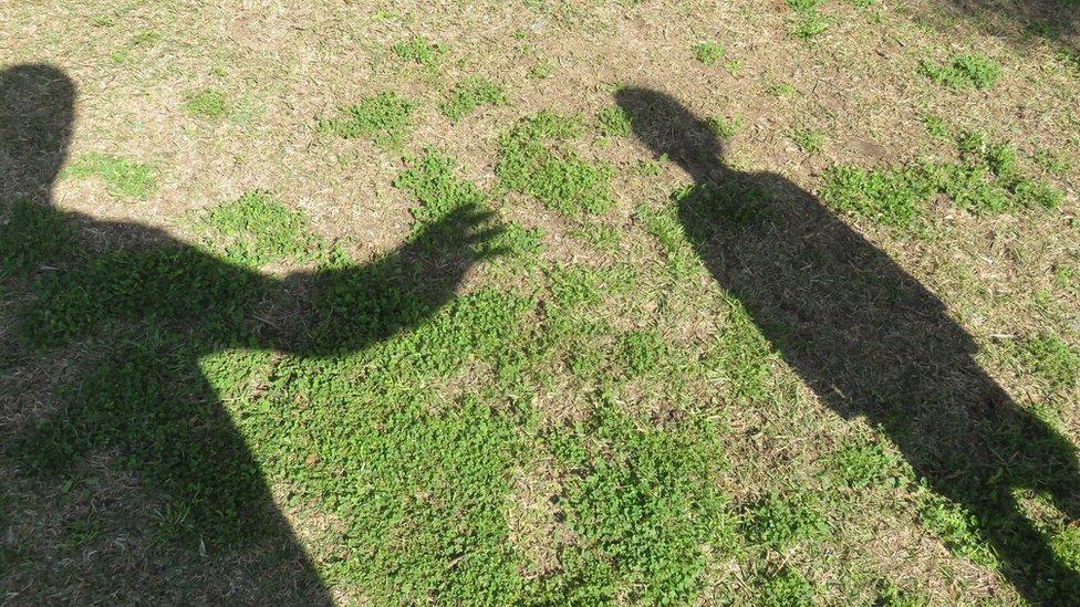 Sombras de un adulto y un niño en señal de ataque