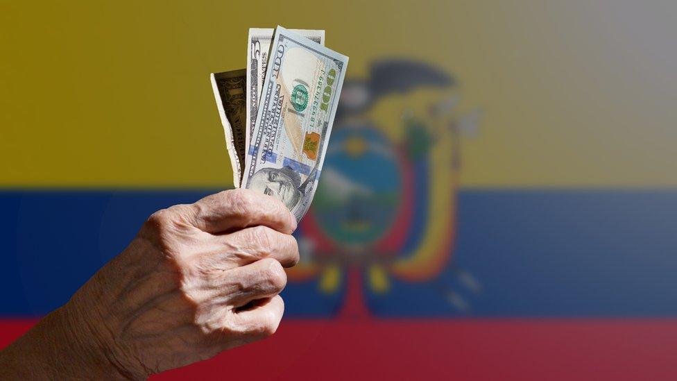 Mano con dólares sobre bandera de Ecuador