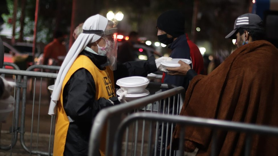À noite, freira com face shield e máscara contra coronavírus entrega marmitas para 2 homens