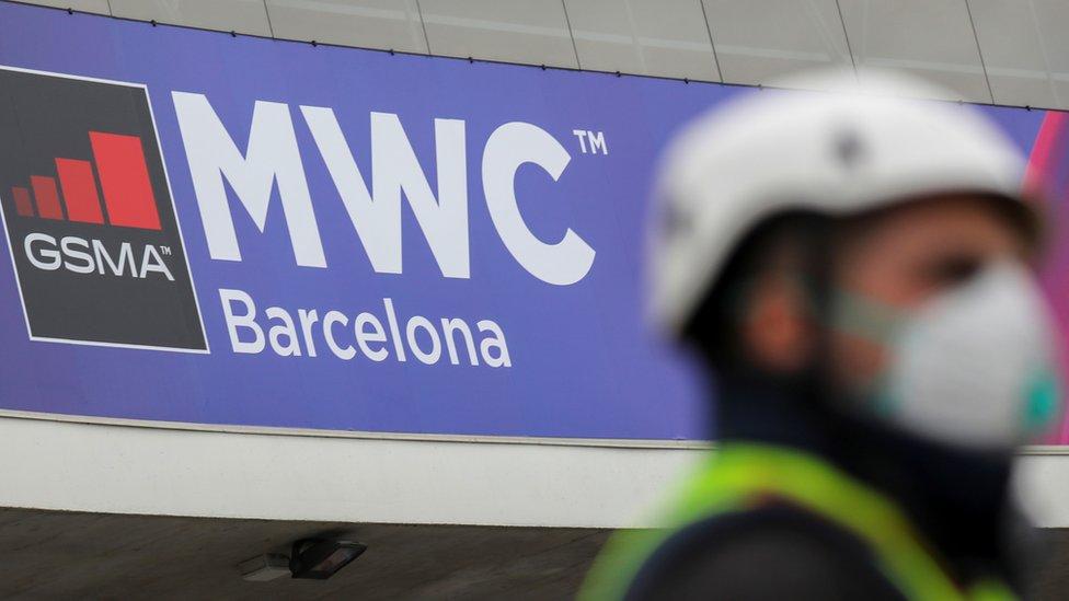 Un hombre con una mascarilla frente a una valla que anuncia el evento de MWC en Barcelona