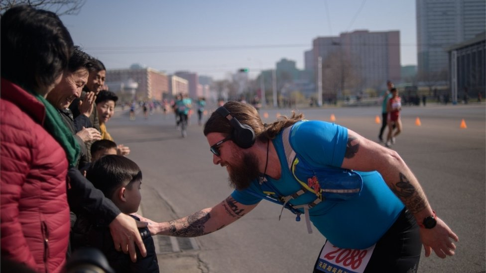 A foreign competitor talks to a child on the roadside of Pyongyang at the marathon on April 7