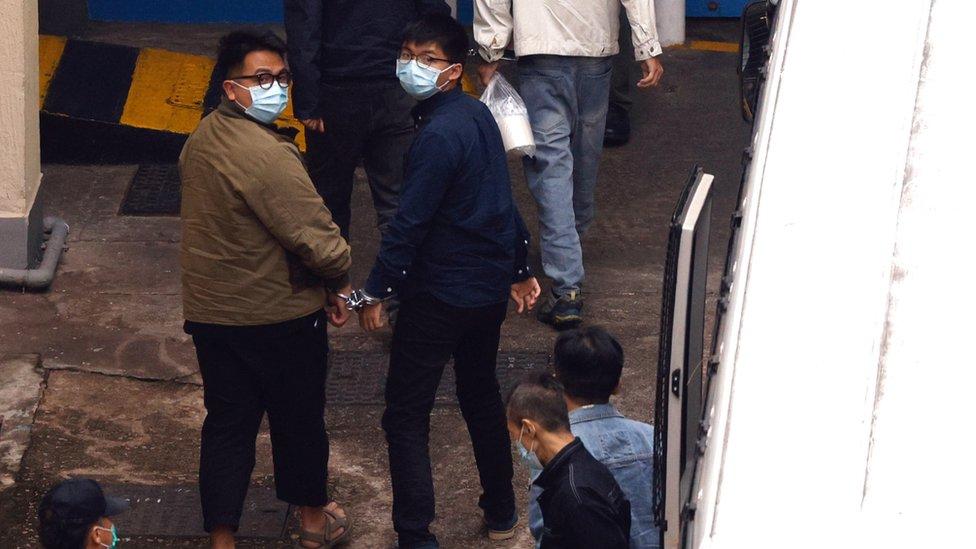 林朗彥(左)與黃之鋒(右)被手扣扣上,步入九龍荔枝角拘留所(23/11/2020)