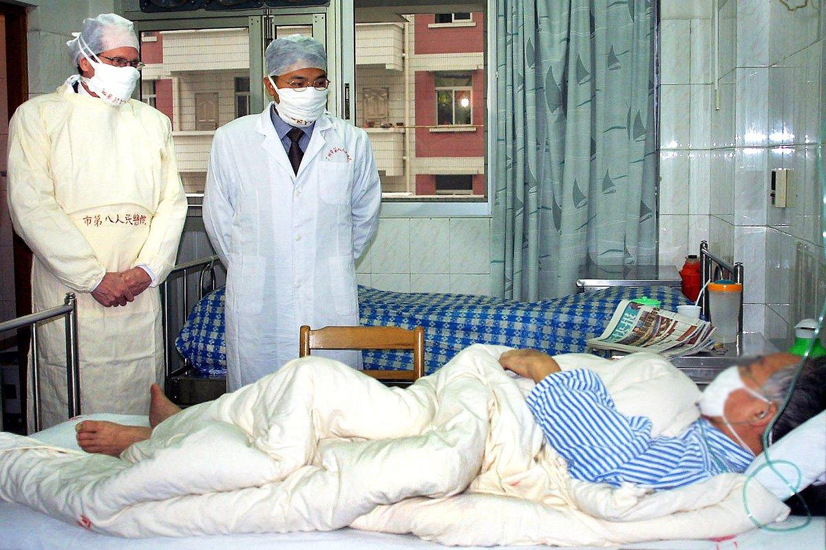 Robert Maguire de la OMS y un médico chino visitan a un paciente con SARS en Guangzhou, China - abril de 2003