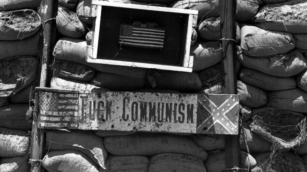 """Un letrero en una posición del ejército de Estados Unidos durante la invasión de Camboya que dice """"A la mierda el comunismo""""."""