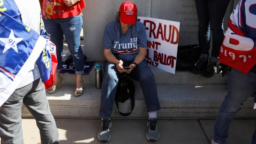A Trump supporter sits on the floor