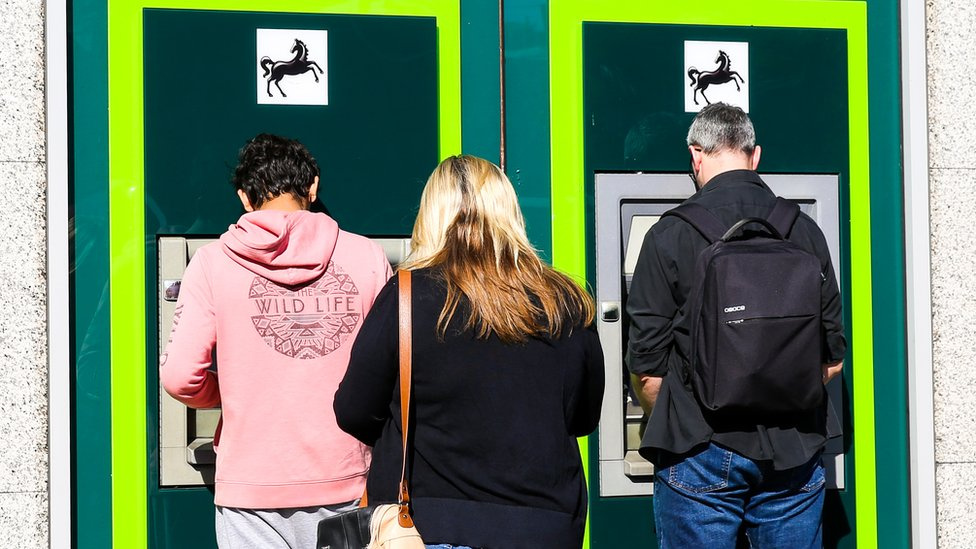 Customers queuing at an ATM