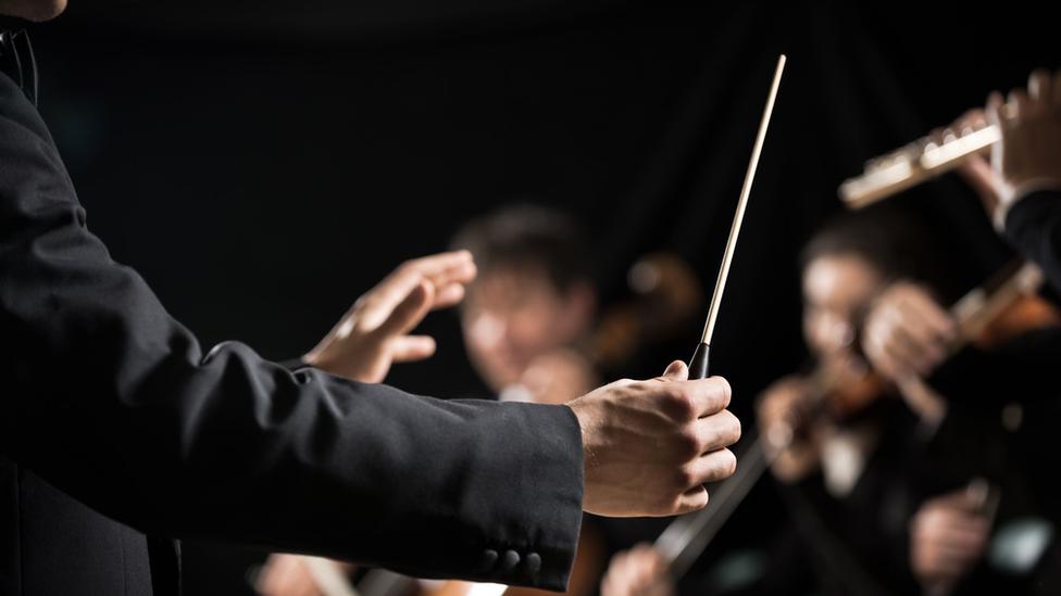 Director dirigiendo una orquesta.