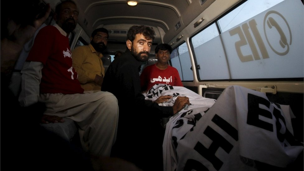 Abdul Majeed, brother of Shafqat Hussain who was convicted of killing a child in 2004, sits in an ambulance beside the body of Safqat after his execution in Karachi, Pakistan, August 4, 2015.