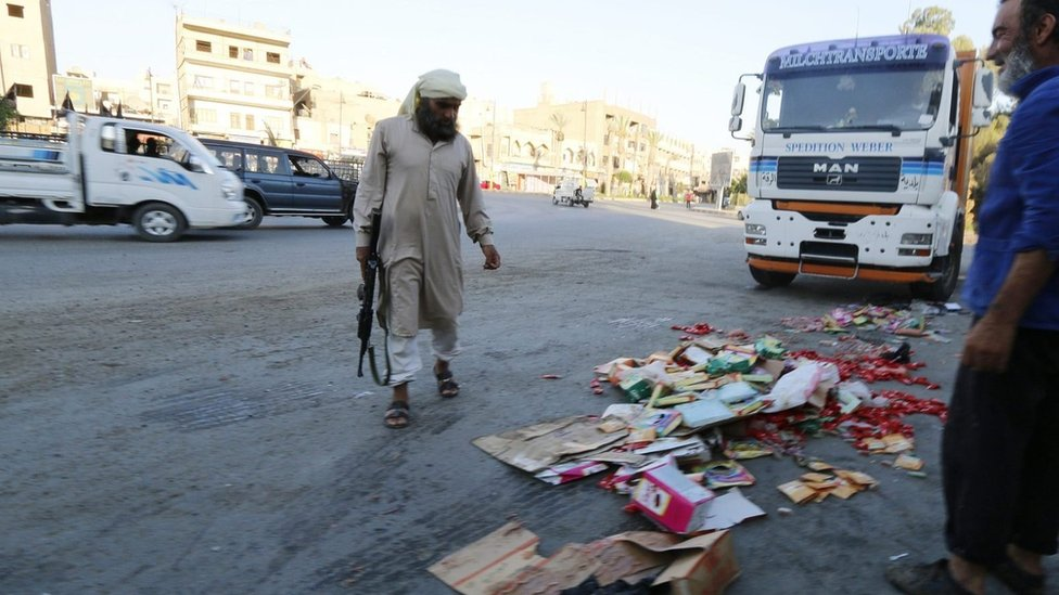 Borac Islamske države baca konfiskovanu robu u Raki, Sirija (14. avgust 2014)