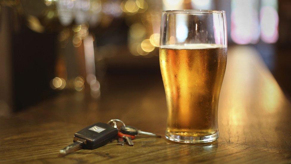 Pint glass on a table with car keys