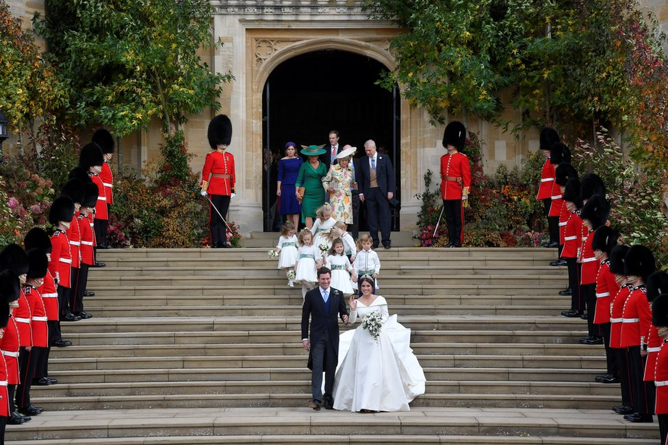 Princess Eugenie of York and her husband Jack Brooksbank walk down the West Steps of St Georg's Chapel
