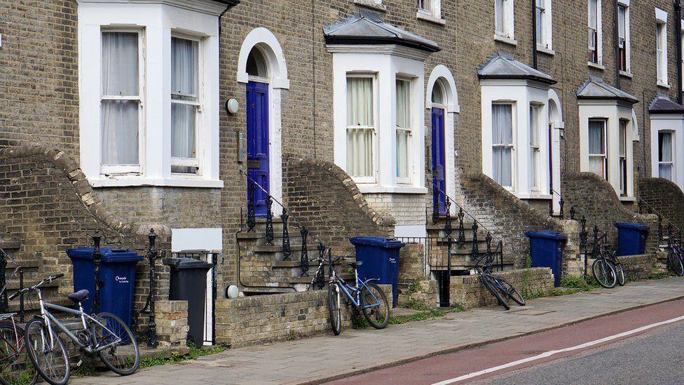 Tachos de basura en la entrada de las casas